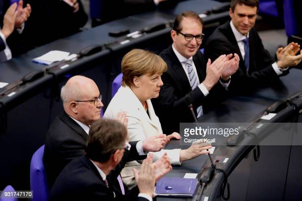 German Chancellor Angela Merkel receives applause from parliamentarians following her election by the Bundestag for a fourth term as chancellor on...