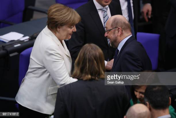 German Chancellor Angela Merkel receives congratulations from Social Democrat Martin Schulz who ran against her in elections last year following...