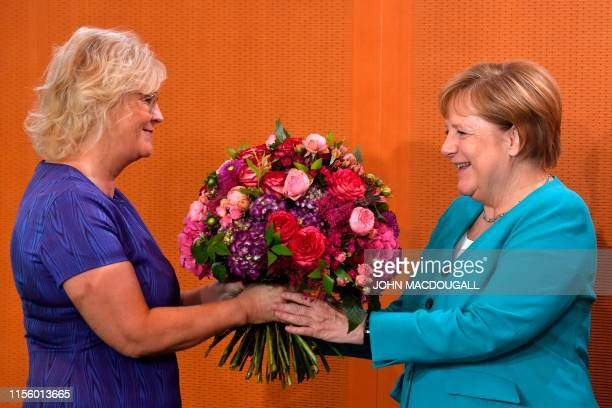German Chancellor Angela Merkel receives flowers for her birthday from Justice Minister Christine Lambrecht during the weekly cabinet meeting on July...