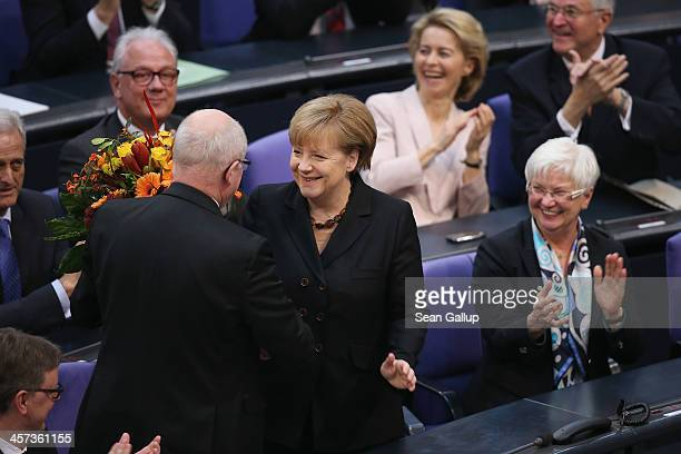 German Chancellor Angela Merkel receives flowers from colleague Volker Kauder who heads the Bundestag faction of the German Christian Democrats...