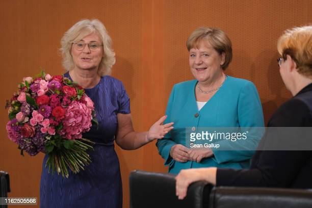 German Chancellor Angela Merkel receives flowers from Justice Minister Christine Lambrecht on the occasion of Merkel's 65th birthday on July 17 2019...
