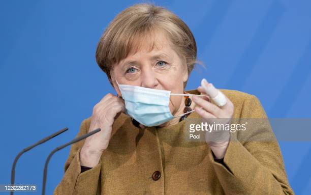 German Chancellor Angela Merkel removes her face covering before making a statement on the latest coronavirus measures after a Cabinet Meeting on...