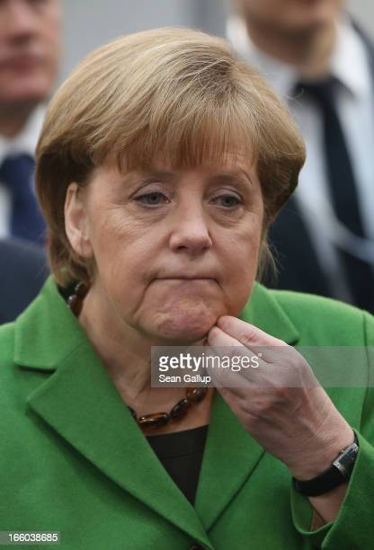 German Chancellor Angela Merkel scratches her chin as she visits the Hannover Messe 2013 industrial trade fair on April 8 2013 in Hanover Germany...