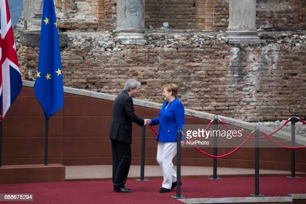 German Chancellor Angela Merkel shake hands with italian prime minister Paolo Gentiloni as she arrives at the Ancient Theatre of Taormina ahead the...