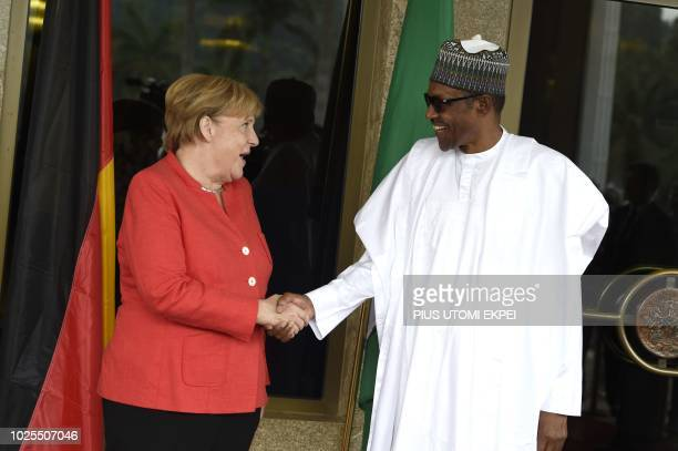 German Chancellor Angela Merkel shakes hand with Nigerian President Mohammadu Buhari on arrival at the presidency in Abuja on August 31 2018 during...