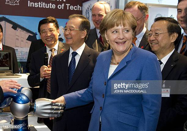 German Chancellor Angela Merkel shakes hands with a robotic arm developed by the Harbin Institute of Technology as Chinese Prime Minister Wen Jiabao...