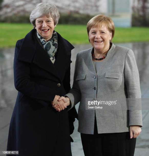 German Chancellor Angela Merkel shakes hands with British Prime Minister Theresa May upon May's arrival for talks at the Chancellery on December 11...