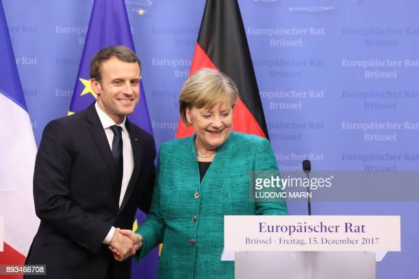 German Chancellor Angela Merkel shakes hands with France's President Emmanuel Macron at the end of a joint press conference at the end of a European...