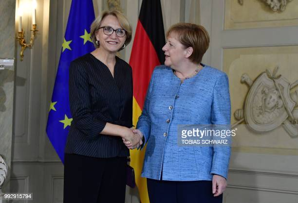 German Chancellor Angela Merkel shakes hands with French ambassador to Germany AnneMarie Descotes at a reception of the diplomatic corps at the...