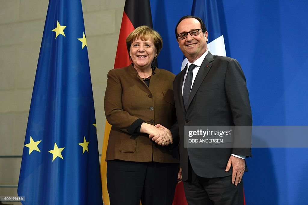 German Chancellor Angela Merkel shakes hands with French President Francois Hollande after a joint press conference on December 13, 2016 at the Chancellery in Berlin. / AFP / ODD