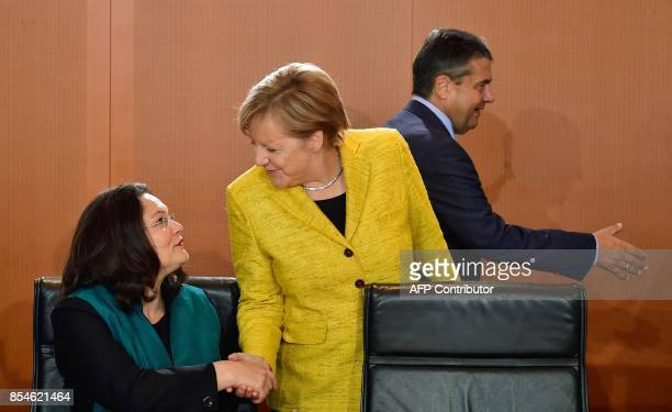German Chancellor Angela Merkel shakes hands with German Labour and Social Minister Andrea Nahles as German Vice Chancellor and Foreign Minister...
