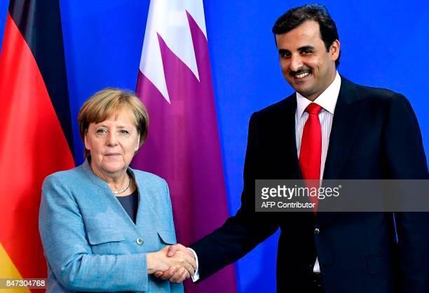 German Chancellor Angela Merkel shakes hands with Qatar's Emir Sheik Tamim bin Hamad alThani after talks at the Chancellery in Berlin on September 15...