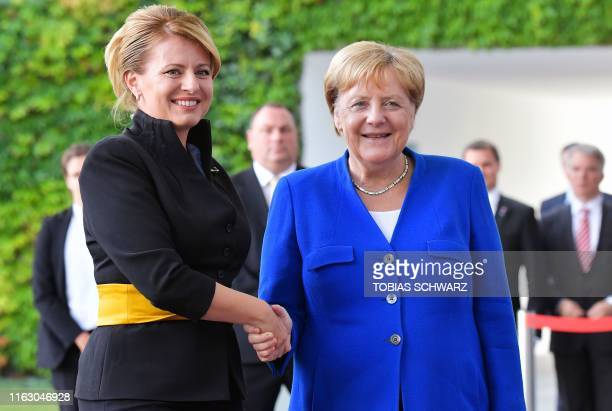 German Chancellor Angela Merkel shakes hands with Slovakia's President Zuzana Caputova as she arrives for a meeting at the Chancellery on August 21...