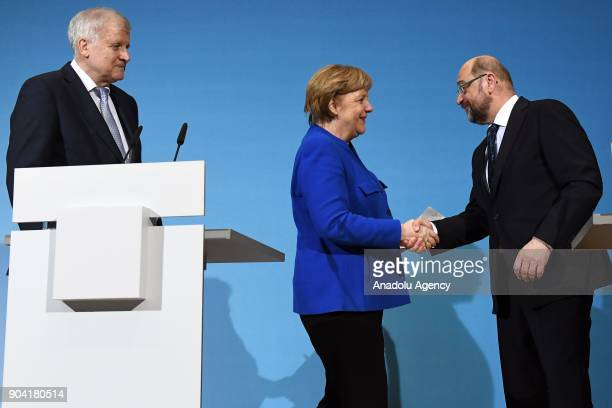 German Chancellor Angela Merkel shakes hands with Social Democratic Party SPD chairman Martin Schulz as they flanked by Bavarian Prime Minister Horst...