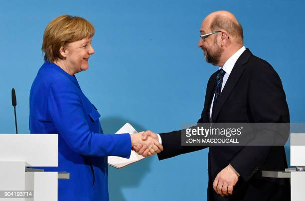German Chancellor Angela Merkel shakes hands with the leader of the Social Democratic Party Martin Schulz at the end of a joint press conference with...