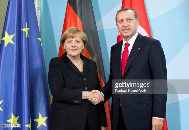 German Chancellor Angela Merkel shakes hands with the Turkish Prime Minister Recep Tayyip Erdogan after attending a joint press conference on October...