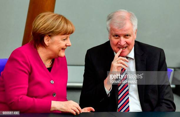 German Chancellor Angela Merkel shares a laugh with German Interior Minister Horst Seehofer before delivering a speech to parliament on March 21 2018...