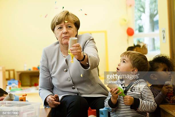 German Chancellor Angela Merkel shoots with a selfmade confetti cannon confetti in the air during her visit to the Weydemeyerstrasse Kindergarten on...