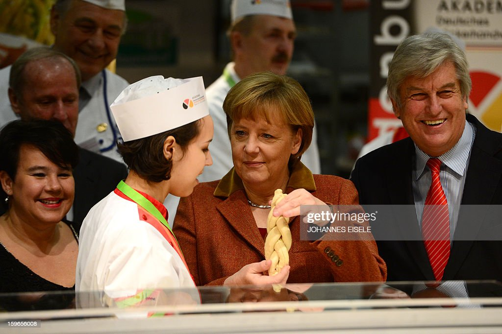 German Chancellor Angela Merkel (C) shows a bread she made at a bakery and pastry booth as she opens the Gruene Woche Agricultural Fair in Berlin on January 18, 2013. This year the official partner country of the fair is The Netherlands. EISELE
