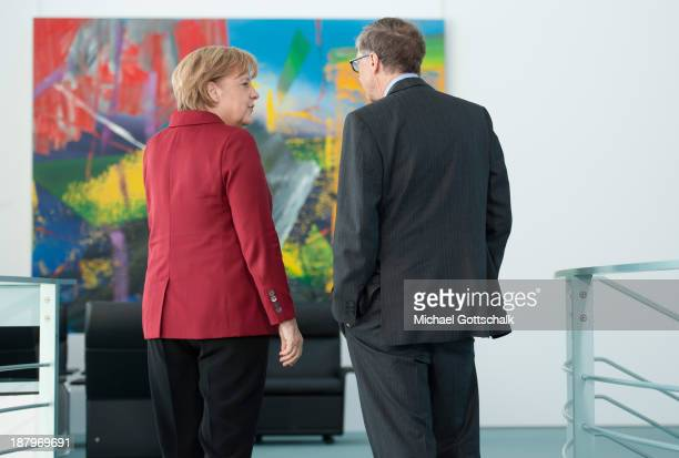 German Chancellor Angela Merkel shows a painting to Bill Gates cofounder of the Bill Melinda Gates Foundation and former head of Microsoft at the...