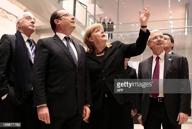 German Chancellor Angela Merkel shows French President Francois Hollande around as they arrive for a joint session of the French National Assembly...