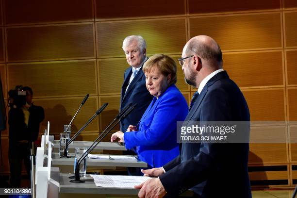 German Chancellor Angela Merkel shows her watch next to the leader of the Christian Social Union Horst Seehofer and the leader of the Social...