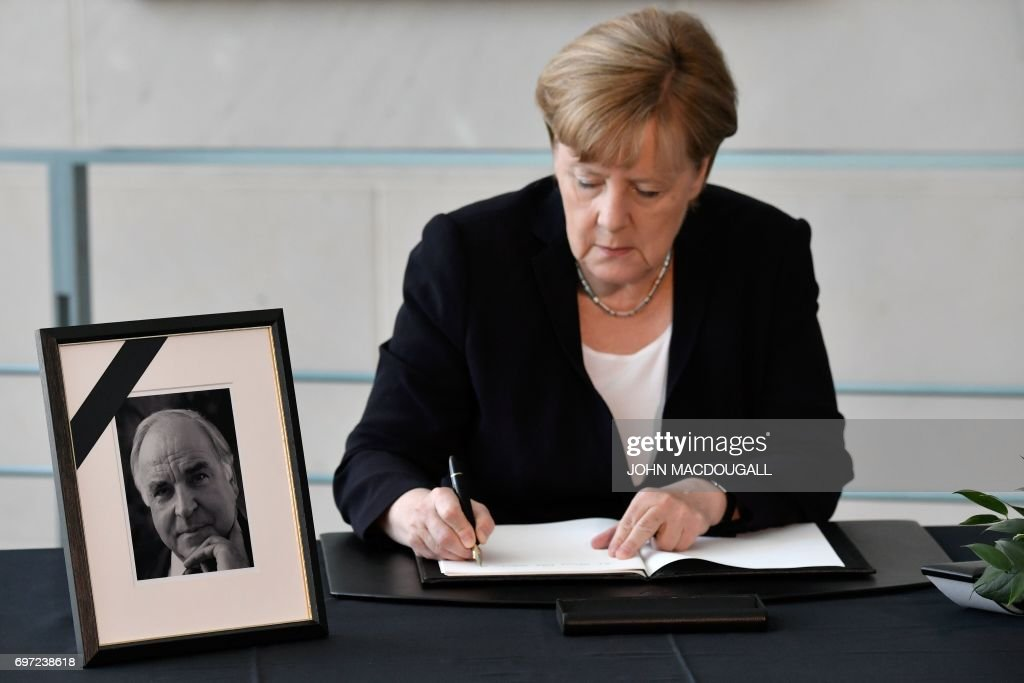 German Chancellor Angela Merkel signs a book of condolence for former German Chancellor Helmut Kohl at the Chancellery in Berlin on June 18, 2017. Helmut Kohl, the former German chancellor who seized the chance to reunite his country after years of Cold War separation, died at the age of 87 on June 16, 2017. / AFP PHOTO / John MACDOUGALL