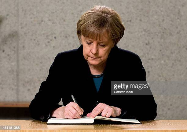 German Chancellor Angela Merkel signs a condolence book in the French Embassy on January 8 2015 in Berlin Germany Twelve people were killed including...