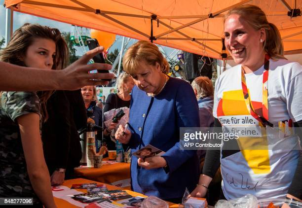 German Chancellor Angela Merkel signs autographs at a neighbourhood fair organised by the local branch of the Christian Democratic Union as she...