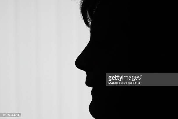 TOPSHOT German Chancellor Angela Merkel silhouettes in front of a window as she briefs the media after a meeting with governors of eastern German...
