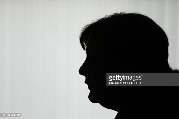 German Chancellor Angela Merkel silhouettes in front of a window as she briefs the media after a meeting with governors of eastern German states at...