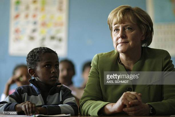 German Chancellor Angela Merkel sits besides children in a classroom as she visits a school for street kids backed by a German charity organisation...