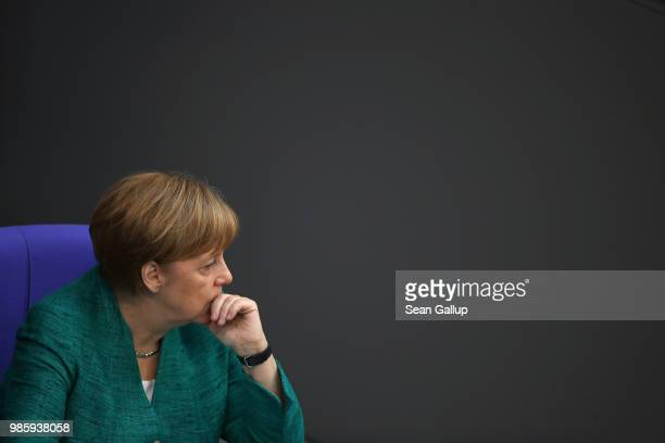German Chancellor Angela Merkel sits don after she gave a government declaration at the Bundestag ahead of the upcoming EU and NATO summits on June...