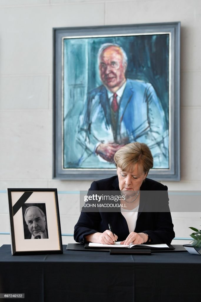 German Chancellor Angela Merkel sits in front of the official portrait of former German Chancellor Helmut Kohl as she signs his book of condolence at the Chancellery in Berlin on June 18, 2017. Helmut Kohl, the former German chancellor who seized the chance to reunite his country after years of Cold War separation, died at the age of 87 on June 16, 2017. / AFP PHOTO / John MACDOUGALL