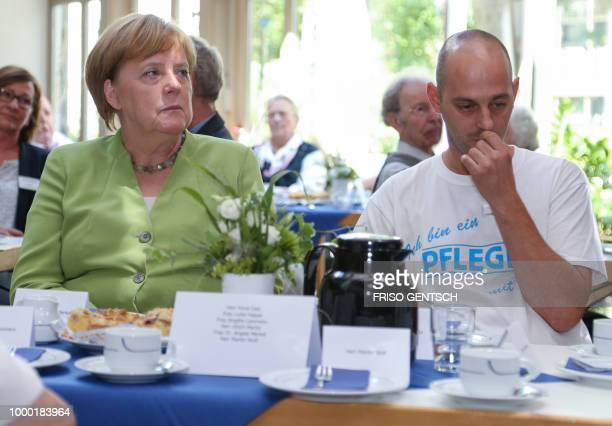 German chancellor Angela Merkel sits next to carer Ferdi Cebi during a visit of the retirement home St Johannisstift in Paderborn on July 16 2018 to...