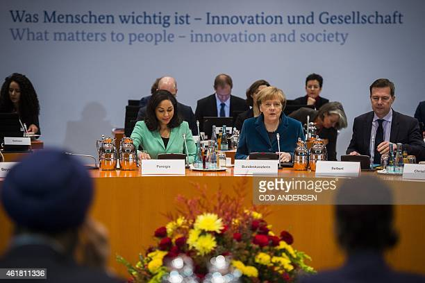 German Chancellor Angela Merkel sits next to Steffen Seibert the spokesperson for the German government and journalist Jana Pareigis as she leads the...