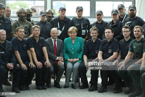German Chancellor Angela Merkel sits with members of German law enforcement and emergency services while thanking them at the conclusion of the G20...