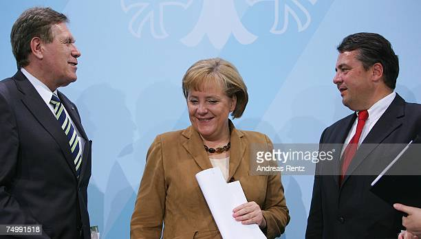 German Chancellor Angela Merkel smiles as Environment Minister Sigmar Gabriel and Economy Minister Michael Glos look on during a press conference...