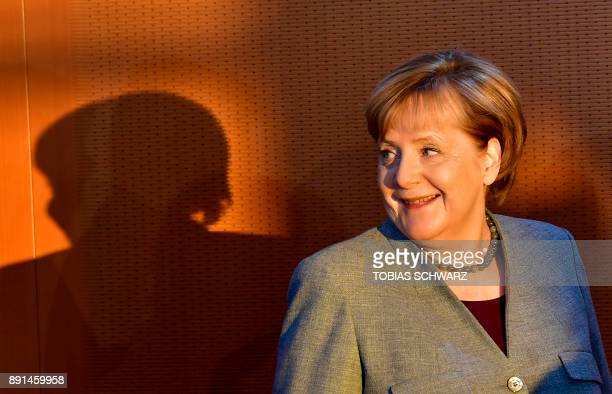 German Chancellor Angela Merkel smiles as she arrives for the weekly cabinet meeting in Berlin on December 13 2017 / AFP PHOTO / TOBIAS SCHWARZ