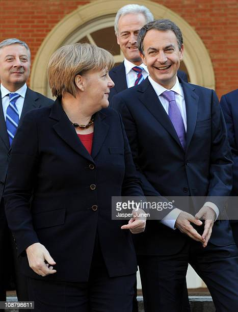 German Chancellor Angela Merkel smiles as she changes sides with Spain's Prime Minister Jose Luis Rodriguez Zapatero as they pose for a family photo...