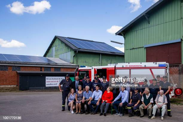 German Chancellor Angela Merkel smiles as she poses for a group photo with local volunteer firemen as she visits the Trede family dairy farm in...