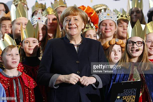 German Chancellor Angela Merkel smiles as she poses with the Epiphany singers in the German Chancellery on January 9 2017 in Berlin Germany As an old...