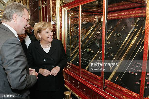 German Chancellor Angela Merkel smiles while looking at jewelry in an exhibit at the Gruenes Gewoelbe Museum while museum director Dirk Syndram looks...