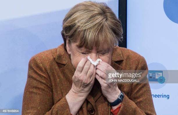 German Chancellor Angela Merkel sneezes as she tours exhibits at a German Information Technology summit in Berlin on November 19 2015 / AFP / JOHN...