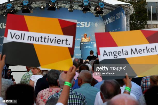 German Chancellor Angela Merkel speaking during a campaign event of the CSU in Erlangen Germany 30 August 2017 In the foreground supporters raising...