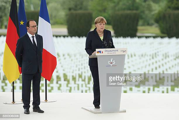 German Chancellor Angela Merkel speaks as French President Francois Hollande looks on during ceremonies to commemorate the 100th anniversary of the...