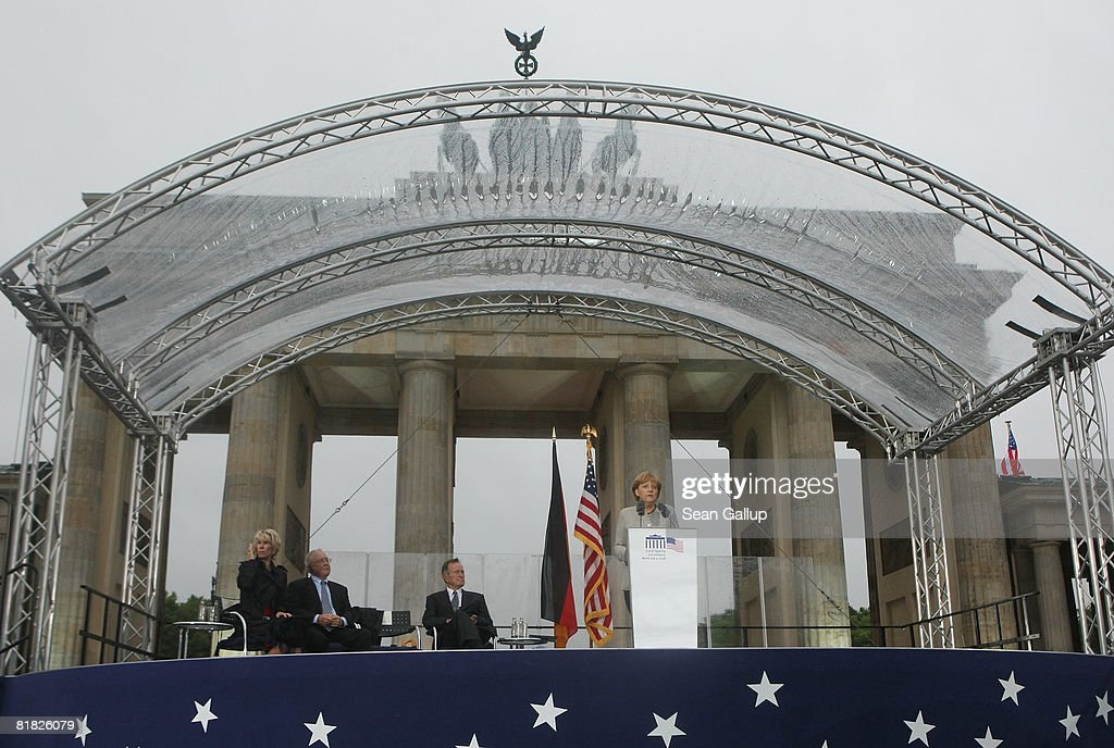 German Chancellor Angela Merkel speaks in front of the Brandenurg Gate as former U.S. President George Bush (C), U.S. Ambassador to Germany William Timken (L) and his wife Sue Timken look on during the official opening ceermony of the new U.S. embassy on July 4, 2008 in Berlin, Germany. Architectural critics claim the embassy, designed by American architect Moore Ruble Yudell, offers little in architectural innovation or design.