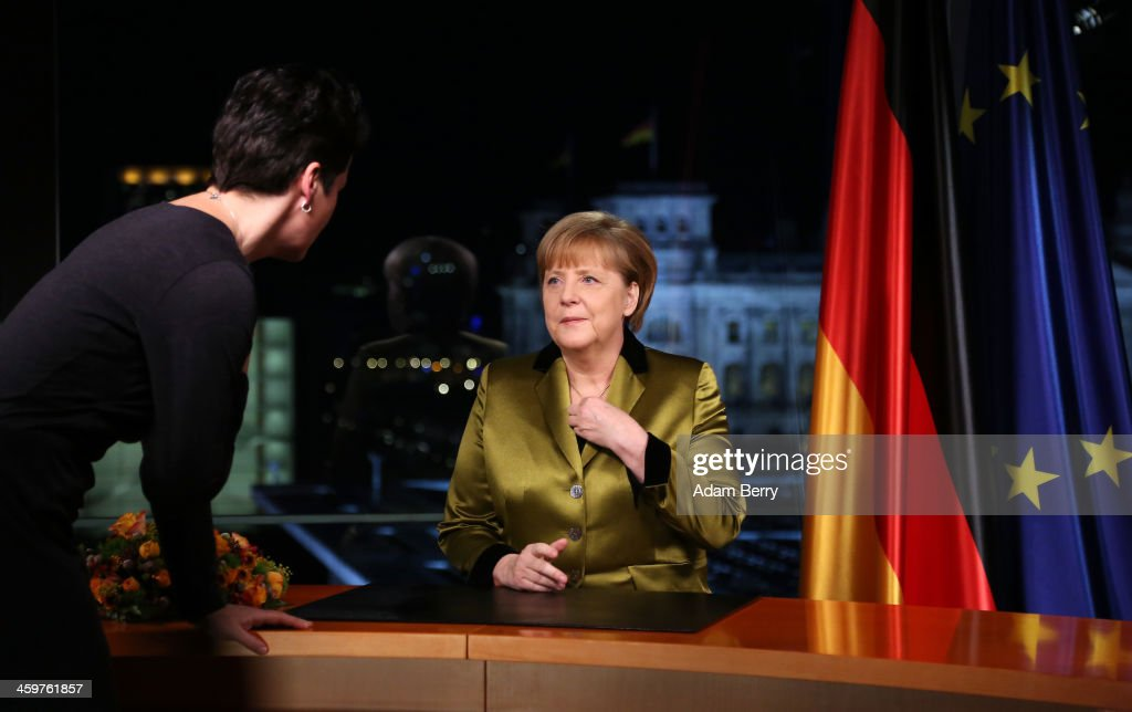 German Chancellor Angela Merkel speaks to an assistant moments after giving her New Year's television address to the nation at the federal chancellery (Bundeskanzleramt) on December 30, 2013 in Berlin, Germany. Merkel spoke of the challenges and priorities set for the German government for 2014.
