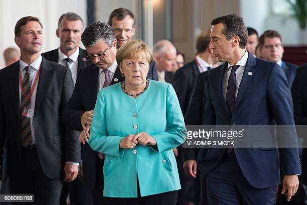 German Chancellor Angela Merkel speaks to Austrian Chancellor Christian Kern as they walk to the family picture shooting after a first working...