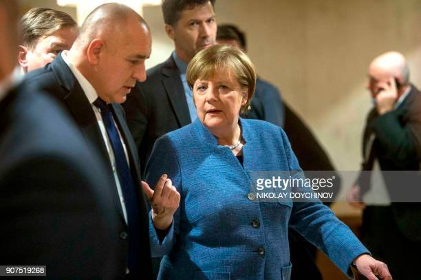 German Chancellor Angela Merkel speaks to Bulgarian Prime Minister Boyko Borisov after their joint press conference in Sofia on January 20 2018 / AFP...